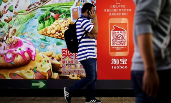 A Chinese man talks on a mobile phone as he walks past a Taobao's mobile app advertisement billboard on display inside a subway station in Beijing.