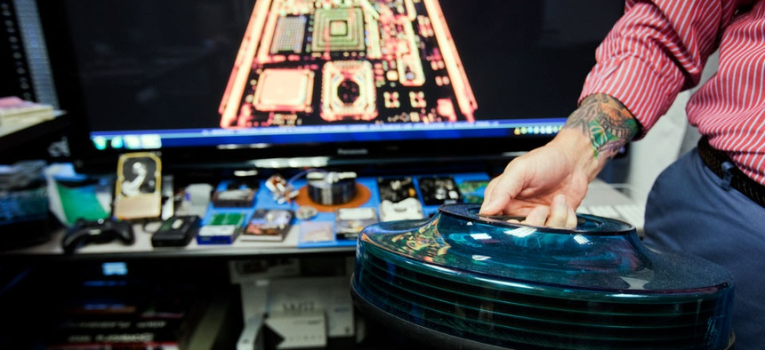 A specialist holds a hard drive seized during the Gulf War, at the Defense Computer Forensics Laboratory, Wednesday, Sept. 10, 2014, in Linthicum, Md. The DCFL is ground zero in the nation's fight against cybercrime.
