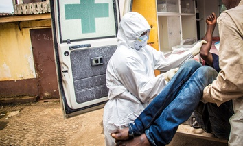 A health worker, center, loads a suspected Ebola patient into the back of a ambulance in Freetown, Sierra Leone.