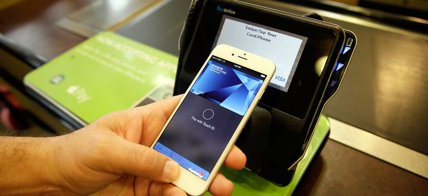 Eddy Cue, Apple Senior Vice President of Internet Software and Services, demonstrates the new Apple Pay mobile payment system at a Whole Foods store in Cupertino, Calif.