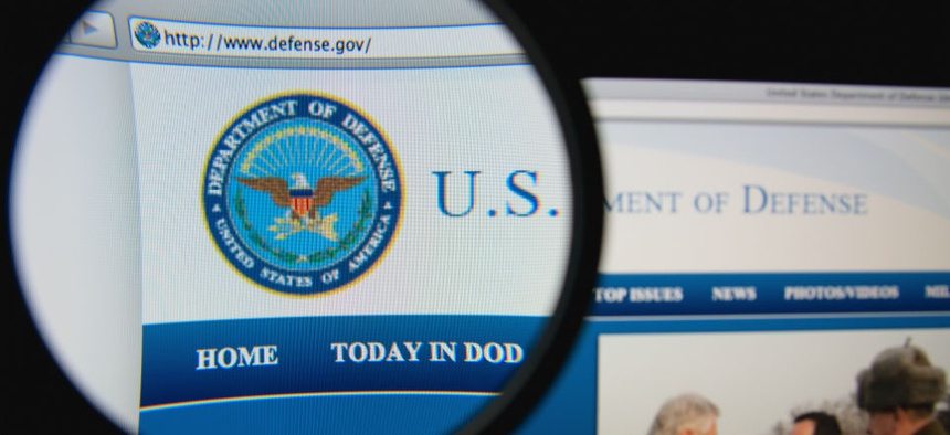 Photo of the United States Department of Defense homepage on a monitor screen through a magnifying glass.
