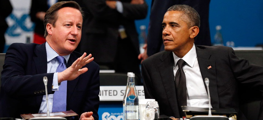 U.S. President Barack Obama, right, and British Prime Minister David Cameron talk at the start of the plenary session at the G20 Summit in Brisbane, Australia Saturday, Nov. 15, 2014.