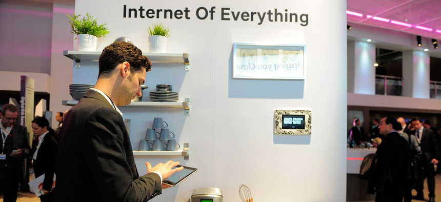 "A man checks his device in front of a banner ""Internet of Everything"" at the Mobile World Congress."