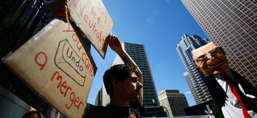 Protesters demonstrate across the street from the Comcast Center Monday, Sept. 15, 2014.