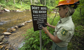 The work of the US Forest Service: Pisgah National Forest Forest Service biologist Lorie Stroup installs a sign to remind forest users about the sensitivity of streambed habitats.