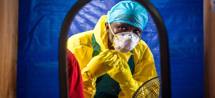 A healthcare worker dons protective gear before entering an Ebola treatment center in Freetown, Sierra Leone.