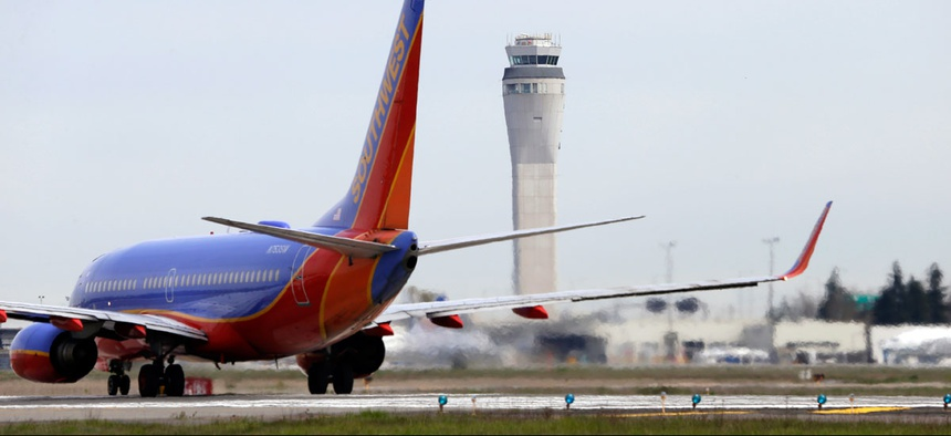 A Southwest airlines jet waiting to depart in view of the air traffic control tower at Seattle-Tacoma International Airport.