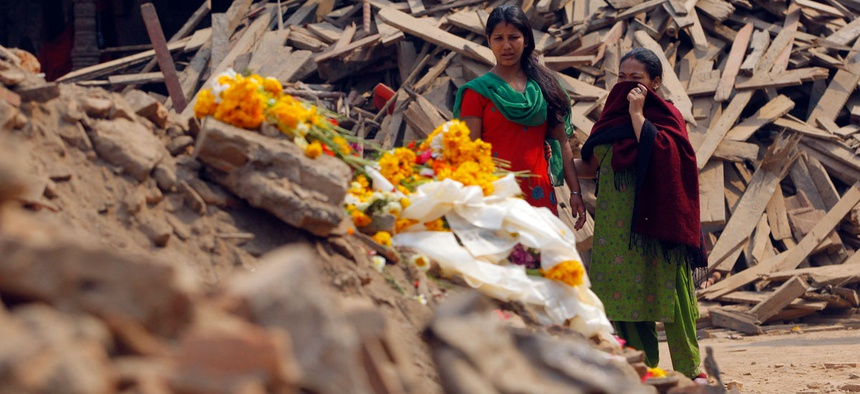 Nepalese women look at floral tributes placed in memory of victims killed in last week's earthquake, at Basantapur Durbar Square in Kathmandu, Nepal.