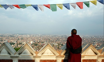 A Buddhist monk catches an aerial view of Kathmandu from the damaged Swayambhunath Stupa premises in Kathmandu, Nepal.