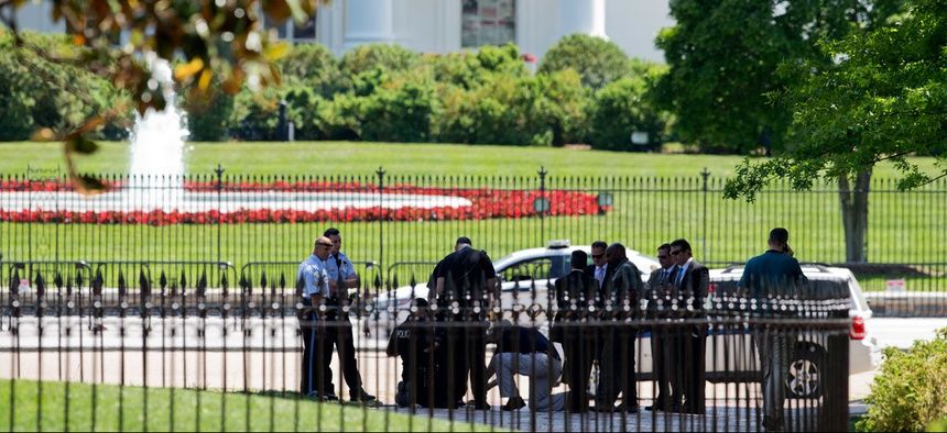 Security personnel are gathered at Lafayette Park near the White House in Washington, Thursday, May 14, 2015 during a lockdown. A federal law enforcement official says a man has been arrested after trying to launch a drone outside the White House fence.