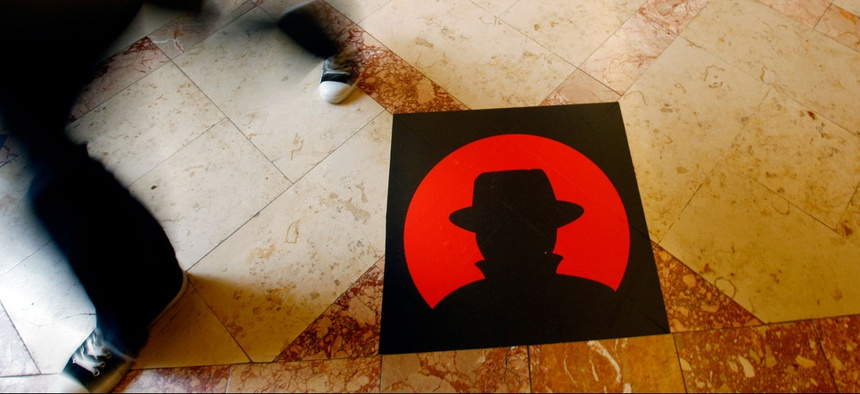 A man passes a logo of the Black Hat technology conference in Las Vegas.