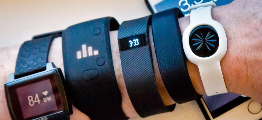 Fitness trackers, from left, Basis Peak, Adidas Fit Smart, Fitbit Charge, Sony SmartBand, and Jawbone Move, are posed for a photo next to an iPhone.