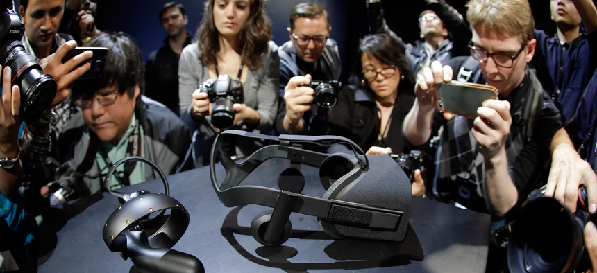Photographers take pictures of the new Oculus Rift virtual reality headset and touch input device.