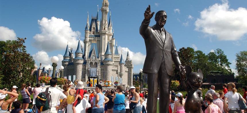 Tourists crowd around Cinderella's Castle to watch a performance at Walt Disney World's Magic Kingdom in Lake Buena Vista, Fla.