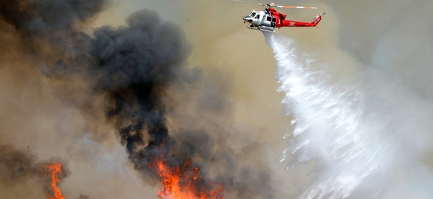A Los Angeles City Fire helicopter drops water on flames, Wednesday, June 24, 2015, in Santa Clarita, Calif.