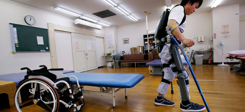 Yuichi Imahata walks using a robotic exoskeleton called ReWalk at Kanagawa Rehabilitation Center in Atgugi, west of Tokyo. Imahata, 31, has been using a wheelchair to get around for seven years after a serious spinal-cord injury.