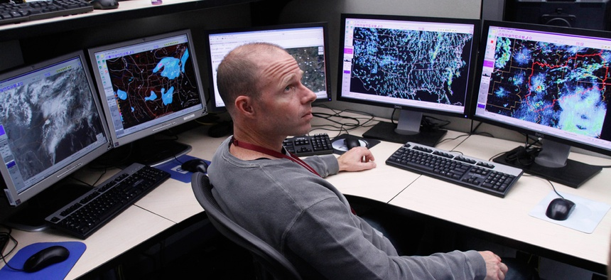 Mark Darrow, a meteorologist at the National Weather Service's Storm Prediction Center, talks to a colleague surrounded by some of the monitors he uses to help forecast storms as he works in the center in Norman, Okla.