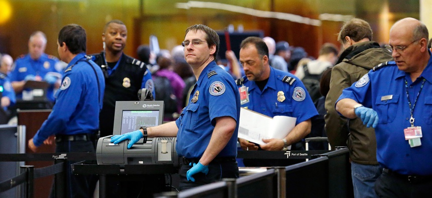 TSA agents work at a security check-point at Seattle-Tacoma International Airport