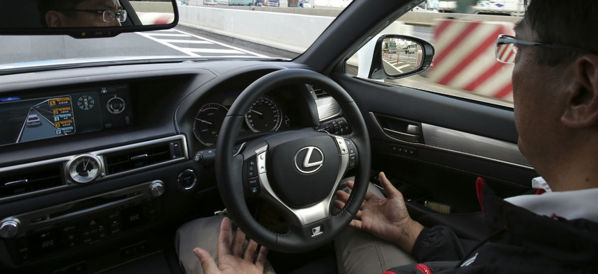 An employee of Toyota Motor Corp., drives automated driving test vehicle during a test drive.