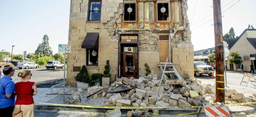 Pedestrians examine a crumbling facade following an earthquake in Napa, California.