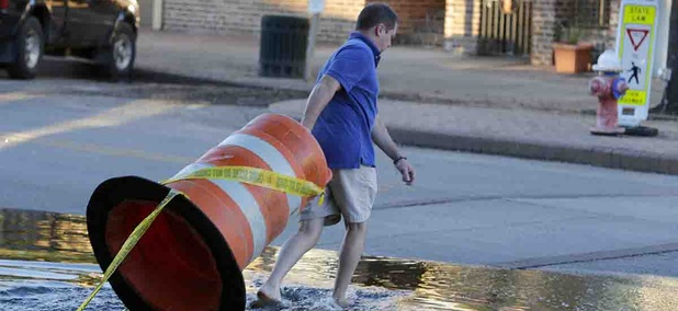 Harris Carter, owner of Castaways & Grill in the historic section of Georgetown, moves a road barrier to block traffic as high tide approaches historic downtown Georgetown, S.C., Thursday, Oct. 8, 2015.