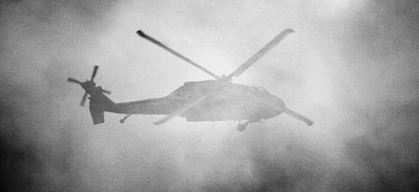 A United States Army Sikorsky UH-60 Blackhawk flies behind a cloud of smoke.