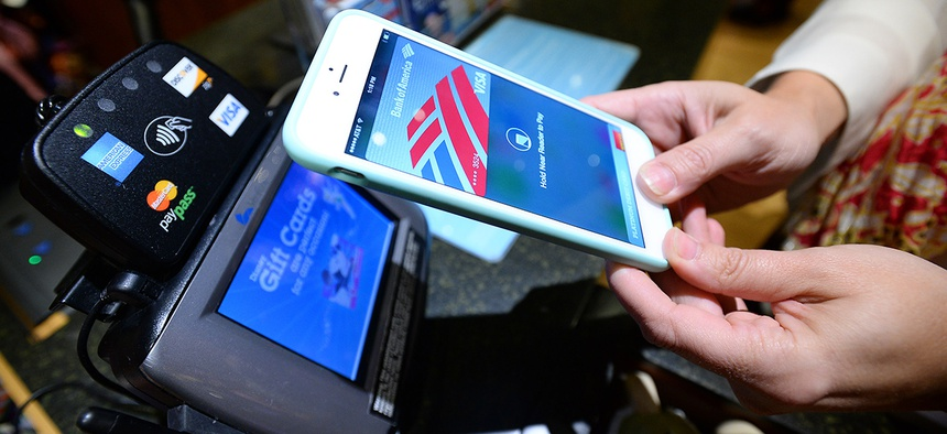 A customer uses Apple Pay at a Disney Store.
