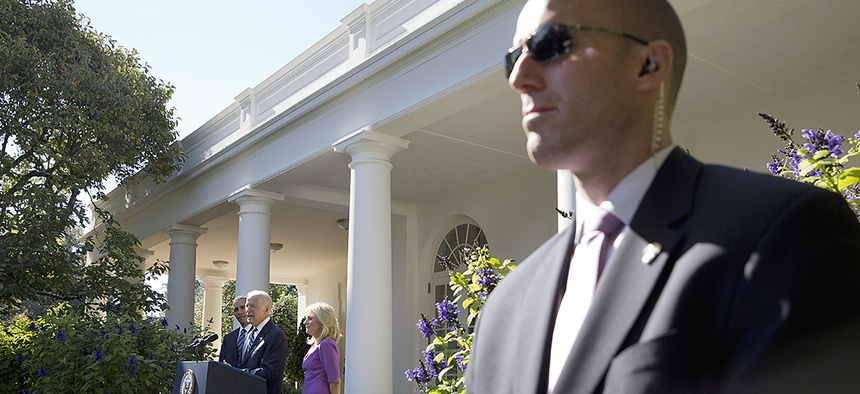 A Secret Service Agent stands guard as Vice President Joe Biden, with President Barack Obama and his wife Jill Biden, speaks in the Rose Garden of the White House.