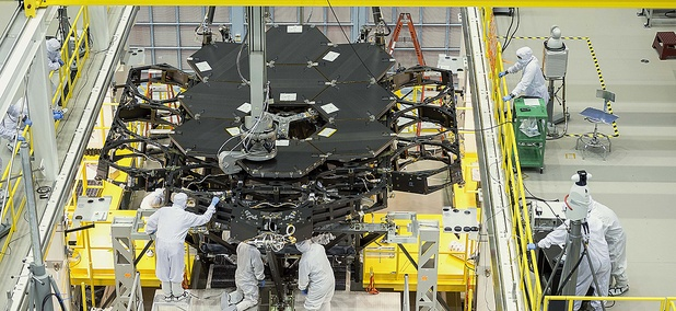 Inside NASA's Goddard Space Flight Center's massive clean room in Greenbelt, Maryland, the ninth flight mirror was installed onto the telescope structure with a robotic arm.