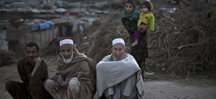 Pakistani men, who were displaced with their families from Pakistan's tribal areas due to fighting between the Taliban and the army, sit on a roadside on the outskirts of Islamabad, Pakistan.