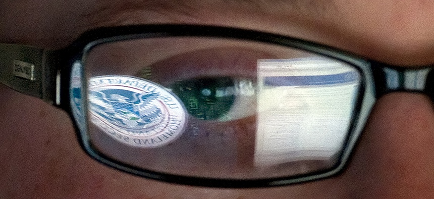 A reflection of the Department of Homeland Security logo is seen reflected in the glasses of a cyber security analyst in the agency's watch and warning center.