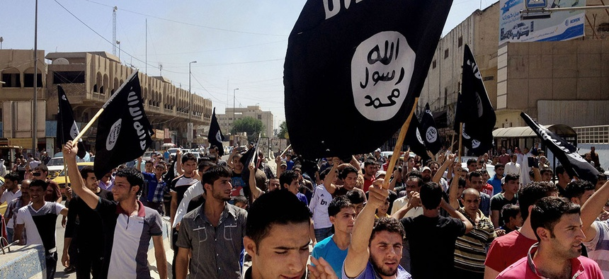 Demonstrators chant ISIS slogans as they carry the group's flags in front of the provincial government headquarters in Mosul.