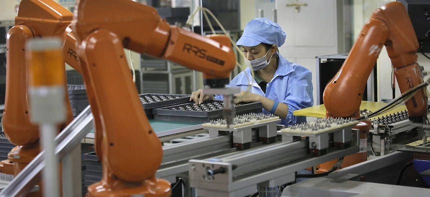 A Chinese woman works amid orange robot arms at Rapoo Technology factory in southern Chinese industrial boomtown of Shenzhen.