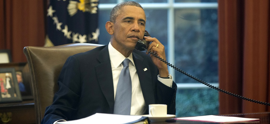 President Obama speaks on a landline phone in the Oval Office.