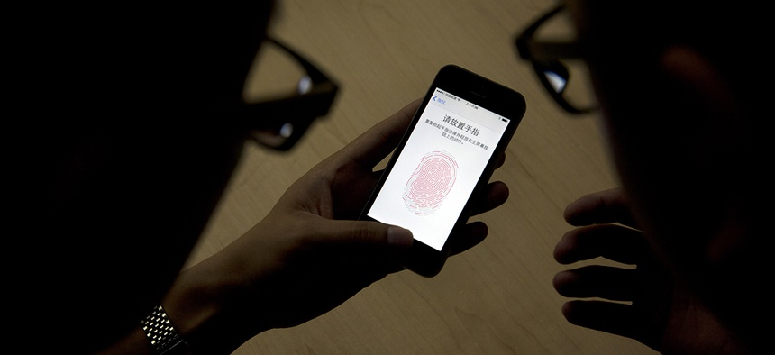 An Apple employee, right, instructs a journalist on the use of the fingerprint scanner technology built into the company's iPhone 5S during a media event in Beijing.