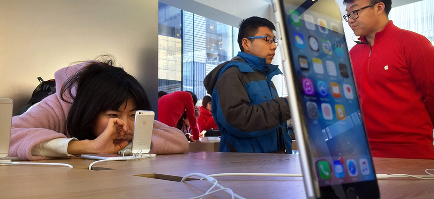 A woman uses a displayed iPhone as a customer talks with an employee, right, at an Apple Store in Beijing, Thursday, Feb. 18, 2016.