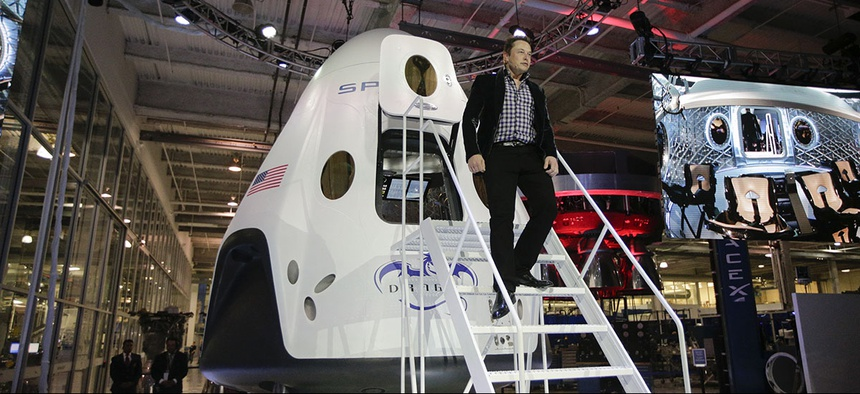 Elon Musk, CEO and CTO of SpaceX, walks down the steps while introducing the SpaceX Dragon V2 spaceship at the company headquarters.