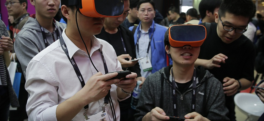 Visitors wearing virtual reality devices play games at a display booth for Qualcomm at the 2016 Global Mobile Internet Conference (GMIC) in Beijing, Thursday, April 28, 2016.