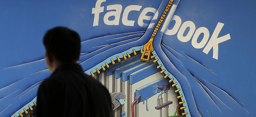 A man walks past a mural in an office on the Facebook campus in Menlo Park, Calif.