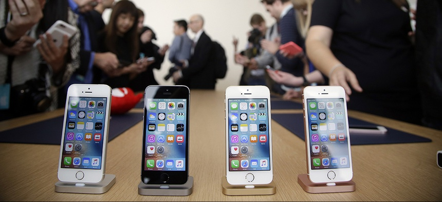 Members of the media and invited guests take a look at the new iPhone SE during an event at Apple headquarters in Cupertino, Calif.