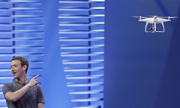 Facebook CEO Mark Zuckerberg points to a drone flying behind him during his keynote address at the F8 Facebook Developer Conference Tuesday, April 12, 2016
