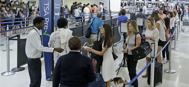 Travelers stand in line as they prepare go to through a Transportation Security Administration checkpoint at Fort Lauderdale-Hollywood International Airport, Friday, May 27, 2016