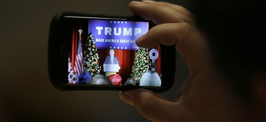 An audience member snaps a cell phone photo as Republican presidential candidate Donald Trump speaks during a campaign rally.