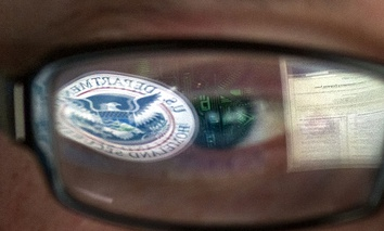 A reflection of the Department of Homeland Security logo is seen reflected in the glasses of a cyber security analyst in the watch and warning center at the Department of Homeland Security's secretive cyber defense facility.
