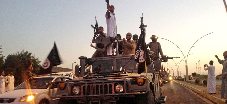 ISIS militants parade in a commandeered Iraqi security forces armored vehicle on a main street in Mosul, Iraq.