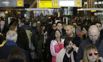 Travelers wait in a winding line to pass through customs and border control at John F. Kennedy Airport in New York.