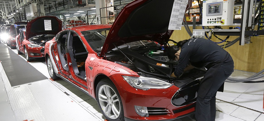 Tesla employees work on a Model S cars in the Tesla factory in Fremont, Calif.
