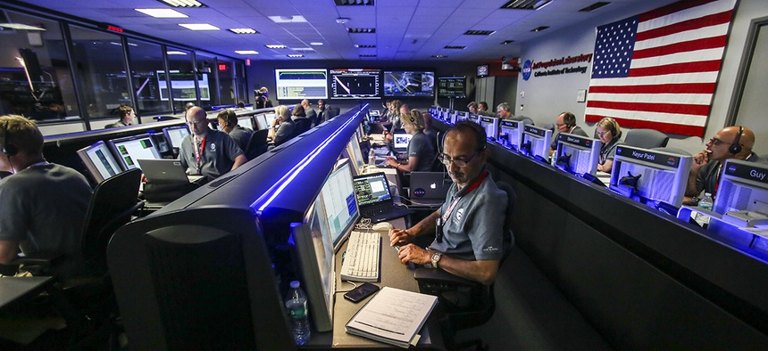 Staff members of Juno Mission watch on before the solar-powered Juno spacecraft went into orbit around Jupiter, at NASA's Jet Propulsion Laboratory in Pasadena, Calif., on July 4, 2016.