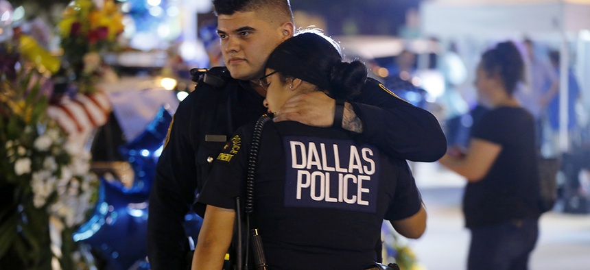 Dallas police officers comfort each other Friday, July 8, 2016, in Dallas in front of police cars decorated as a public memorial in front of police headquarters, in honor of Dallas police who were killed Thursday.