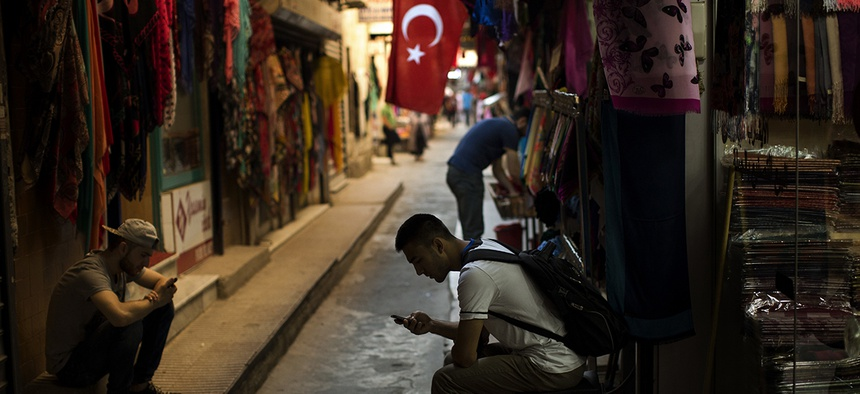 Sellers wait for customers as they look at their phones in central Istanbul, Monday, July 18, 2016.